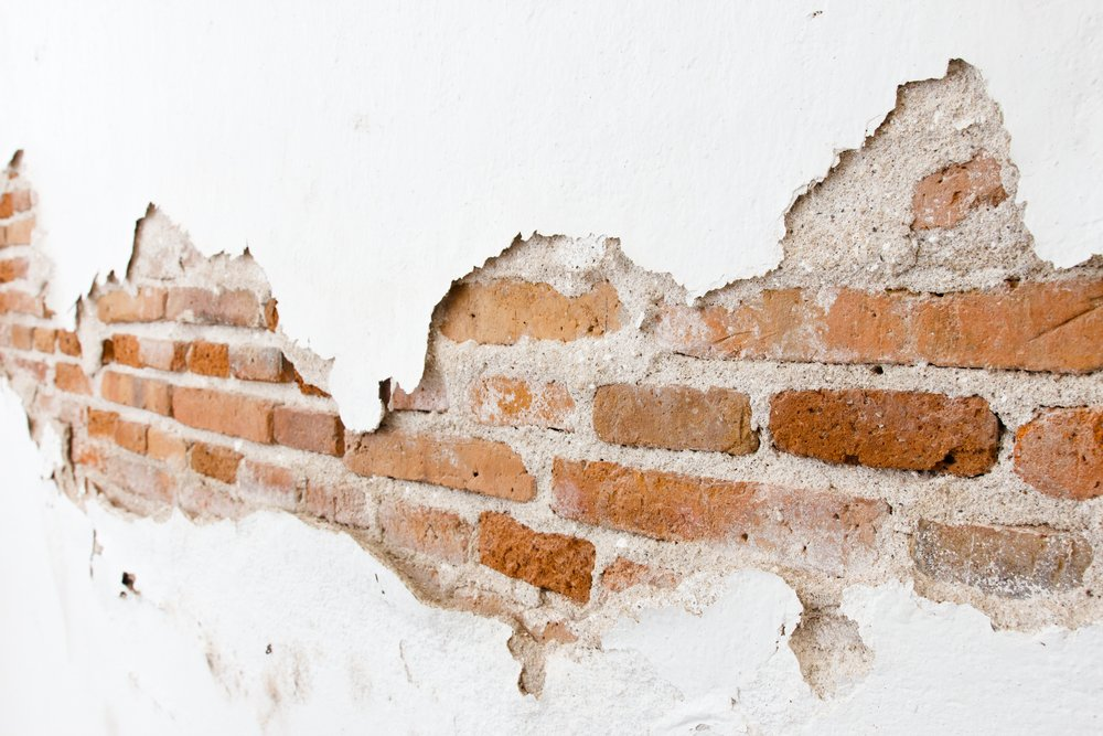 Brick wall partially covered with plaster